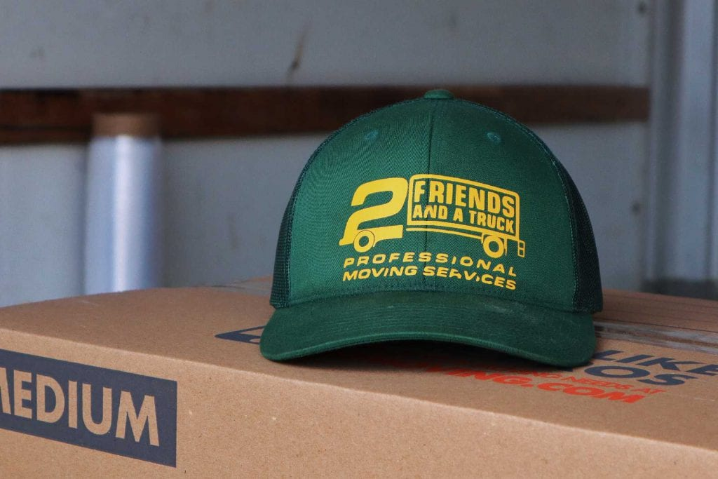 2 friends and a truck logo cap kept on box
